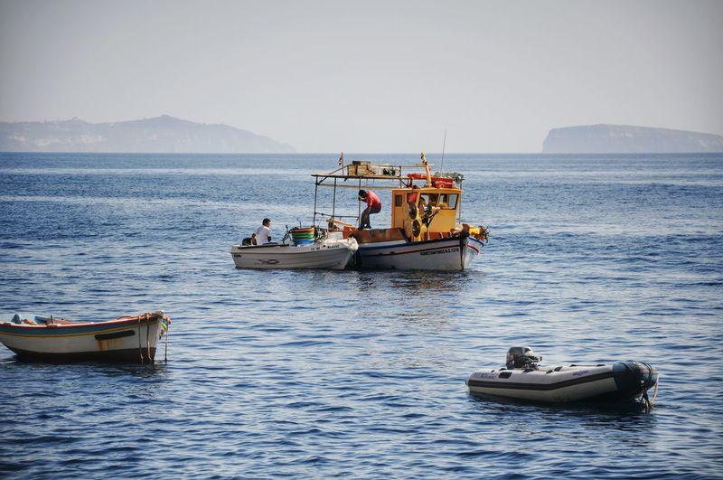 Fishermen fishing in sea against sky