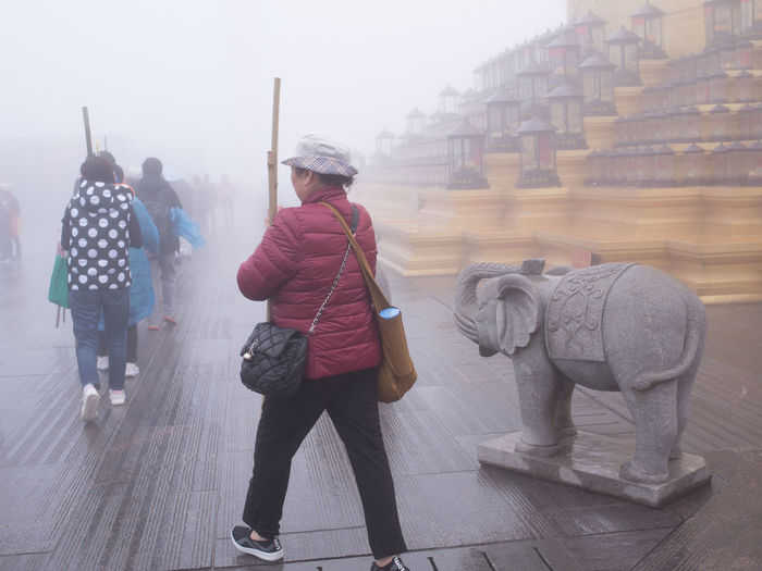 People in a row praying and walking around statue of budda in heavy fog in China. In A Row Statue Tourists Weather Worship Buddist China Cold Elephant Fog Praying Stick Unclear Walking