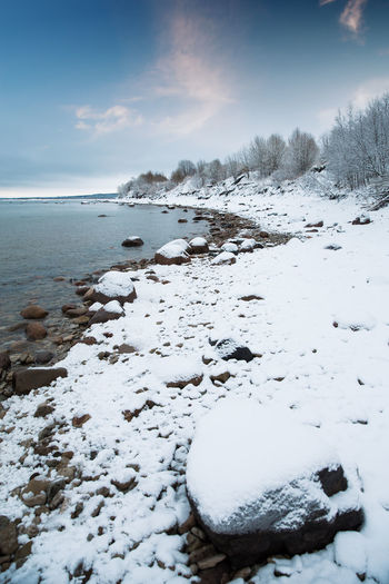 Snow covered land by sea against sky