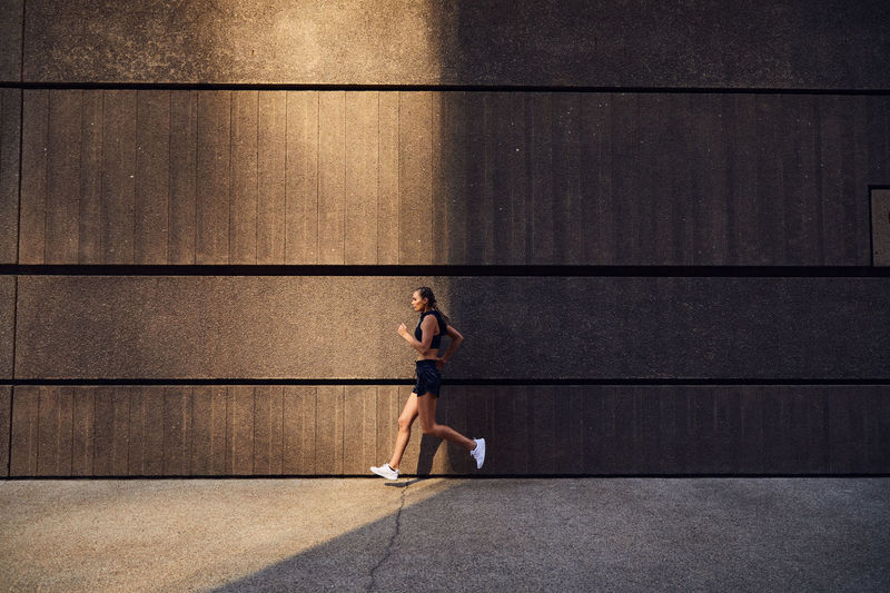 Side view of man running on wall