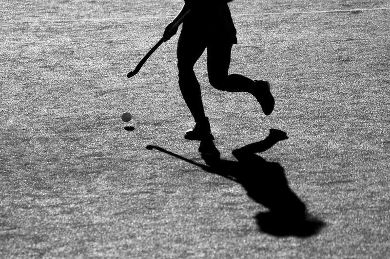 Low Section Of Person Playing Hockey On Field