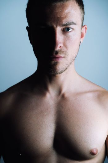 Portrait Of Shirtless Young Man Standing Against Wall At Home