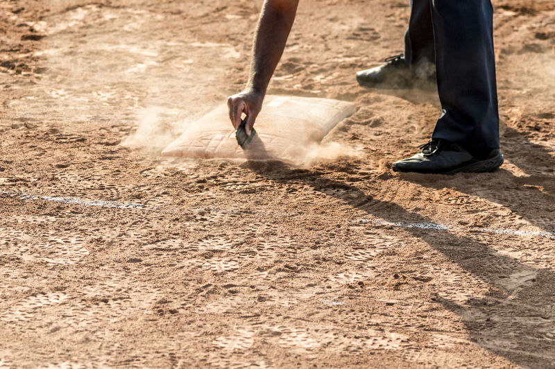 Referee cleans home plate in a baseball (softball) dusty field, with copyspace Adult Body Part Day Dirt Dust Farmer Hand Human Body Part Human Hand Human Leg Human Limb Land Low Section Men Motion Nature Occupation Outdoors People Shadow Sunlight Two People Working