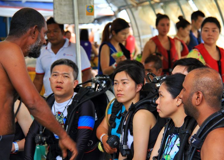 People with scuba tanks listening to instructor