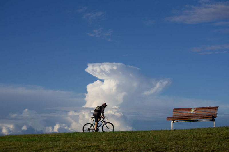 Bicycle Cloud - Sky Cycling Day Field Grass Land Land Vehicle Landscape Leisure Activity Lifestyles Mode Of Transportation Nature One Person Outdoors Real People Ride Riding Sky Transportation