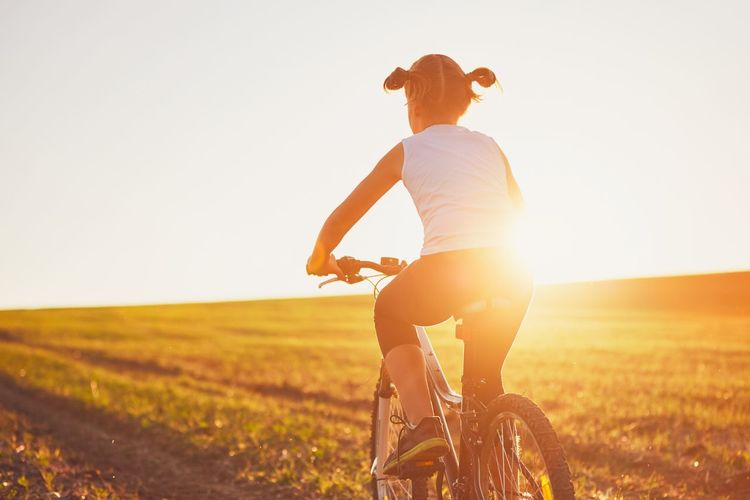 Rear View Of Girl Riding Bicycle On Field Against Clear Sky