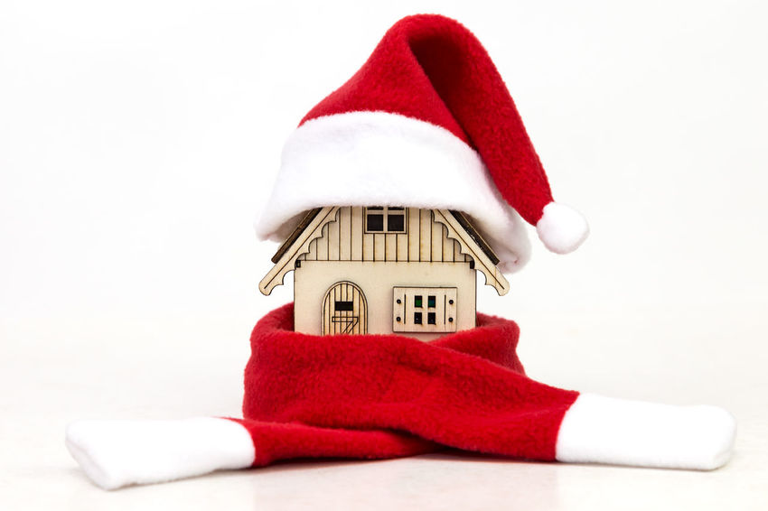 toy wooden house wrapping in red scarf and in red cap Santa Claus on white background Red Cap Santa Christmas Rich Wooden House Prosperity Estate Real Estate Warm Clothing Christmas Decorations New Year Christmas Preparations White Background Gift MAS Xmas Eve Christmas Is Coming Winter Is Coming Red Cap Scarf Wrapped Still Life Buying A House Heating Cold Time No People Headwear