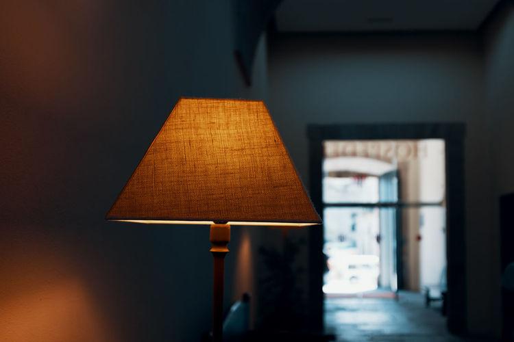 Close-up of illuminated lamp by wall at home