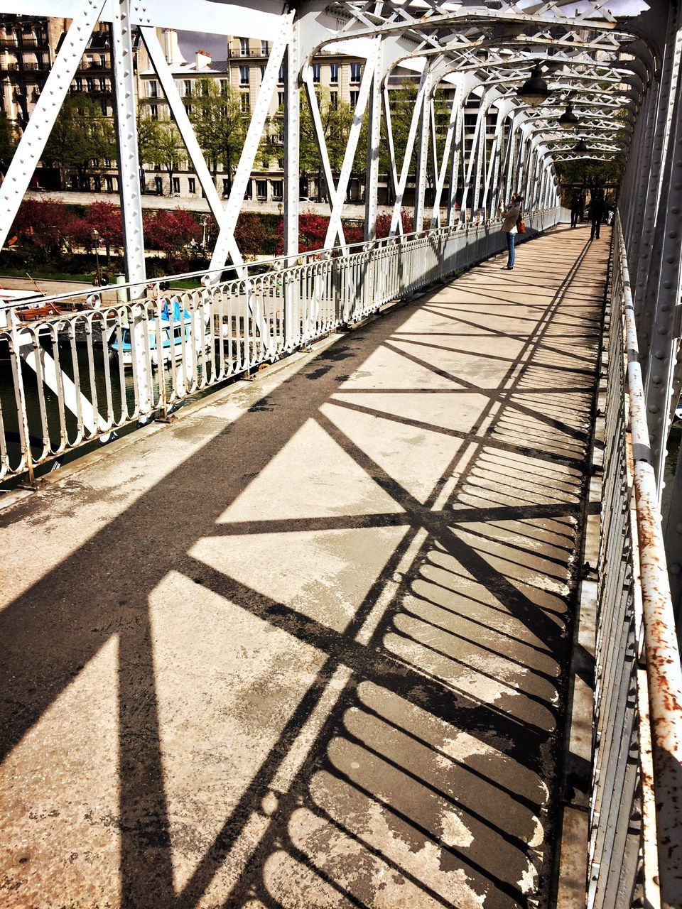 bridge - man made structure, sunlight, connection, architecture, built structure, shadow, railing, day, transportation, footbridge, wood - material, outdoors, no people, girder, city, sky