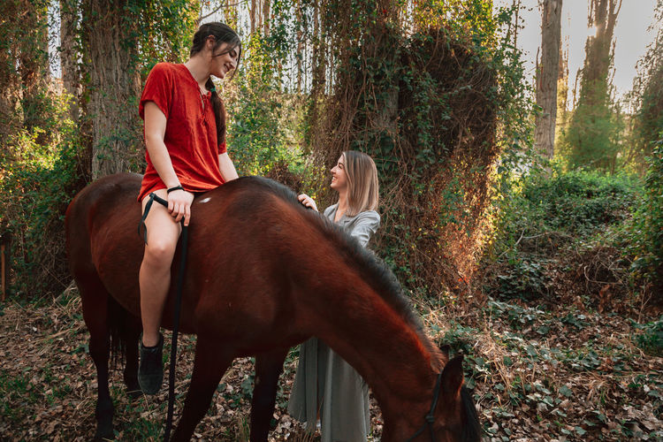 Young woman sitting on horse talking with friend in forest