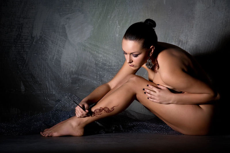 Beautiful young woman applying a temporary tattoo on her leg Ornament Paint Tattooing Woman Adult Applying Art Barefoot Beautiful Woman Beauty Bodyart Drawing Full Length Henna Naked_art Nude_model Nüde Art. One Person Ornate Painting People Sitting Tattoo Young Adult Young Women