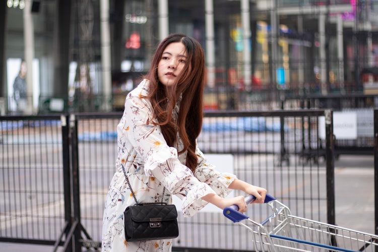 Thoughtful woman standing with shopping cart against mall