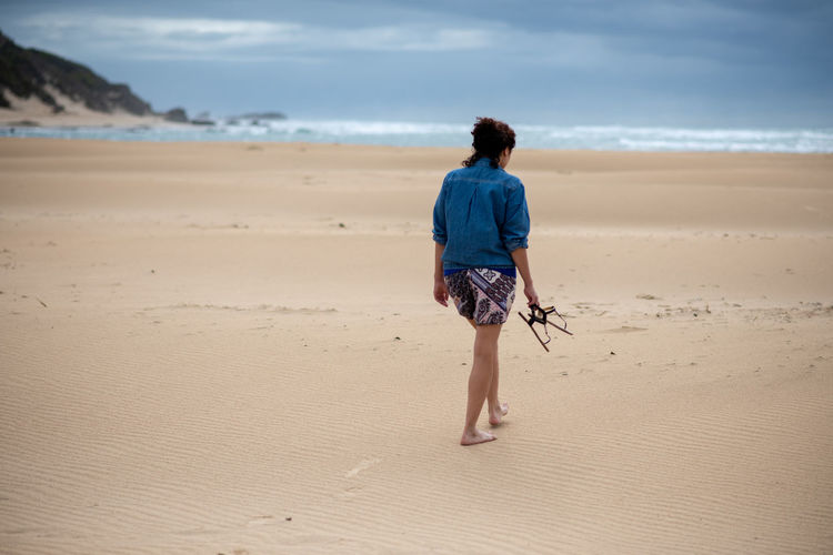 Full length rear view of woman walking on sand at beach