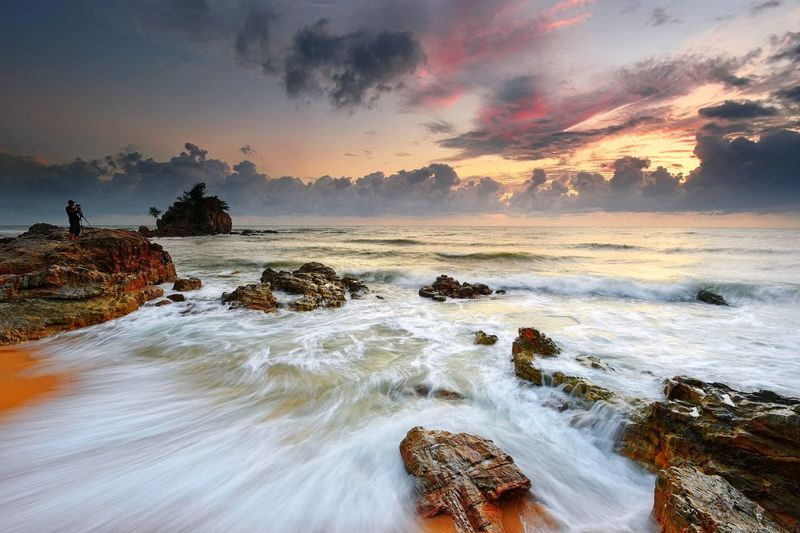Scenic View Of Seascape By Rock During Sunset