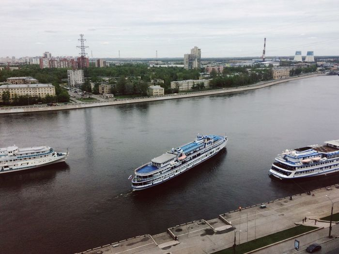 High angle view of boats moored on river in city against sky