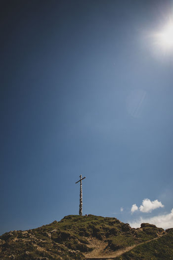 Low angle view of cross on mountain against sky