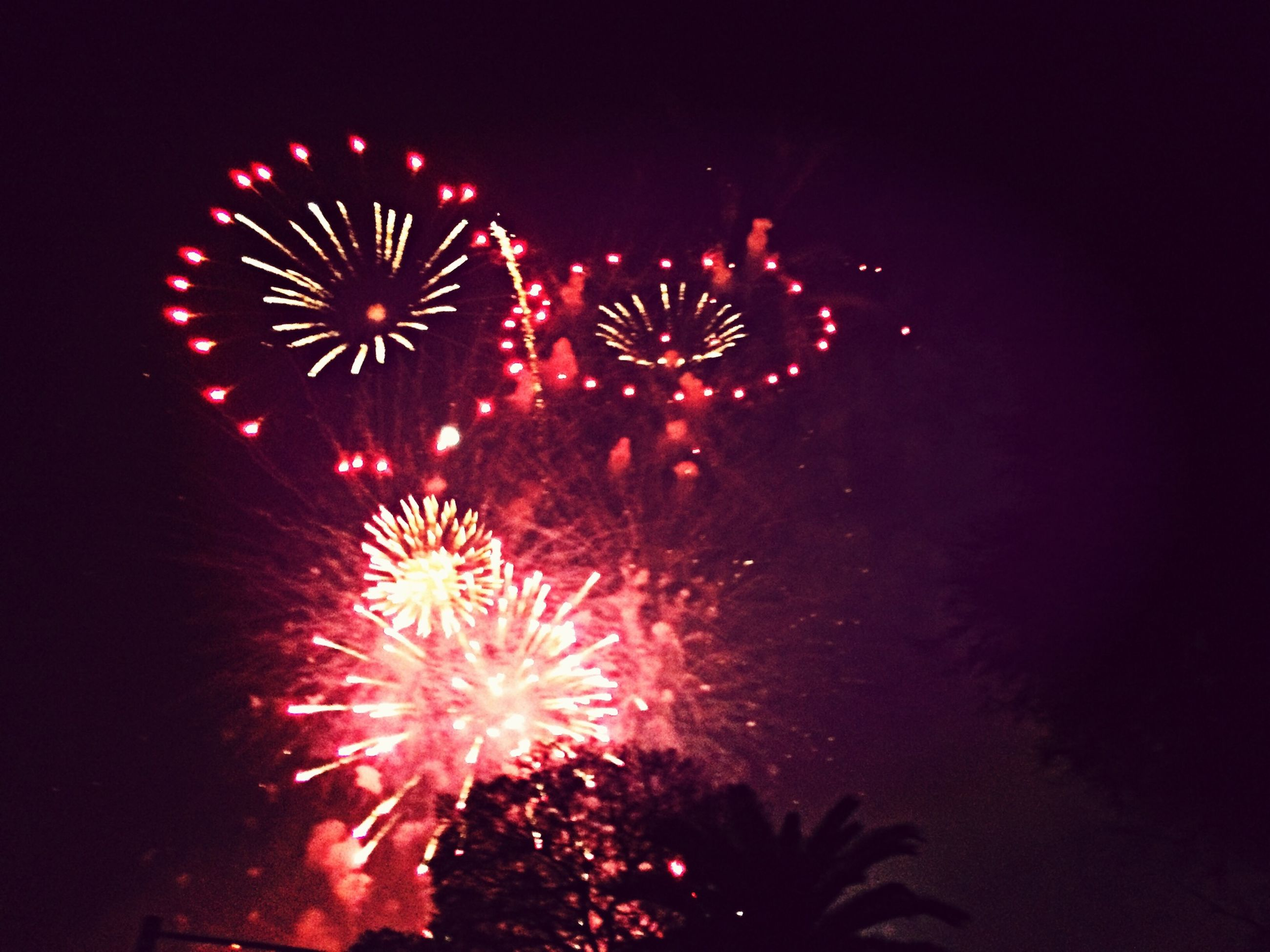 night, celebration, firework display, illuminated, exploding, arts culture and entertainment, firework - man made object, event, glowing, long exposure, motion, entertainment, sparks, celebration event, low angle view, firework, sky, blurred motion, multi colored, fire - natural phenomenon
