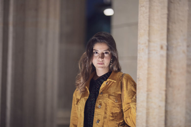 Adult Architectural Column Architecture Beautiful Woman Brown Hair Clothing Focus On Foreground Front View Hair Hairstyle Lifestyles Looking At Camera One Person Portrait Real People Scarf Standing Waist Up Warm Clothing Women Young Adult