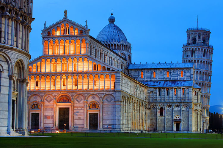 Illuminated pisa cathedral and leaning tower of pisa against clear sky at dusk