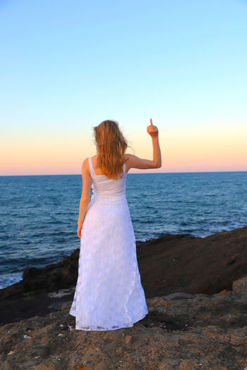 Rear view of woman showing middle finger while standing at beach against during sunset