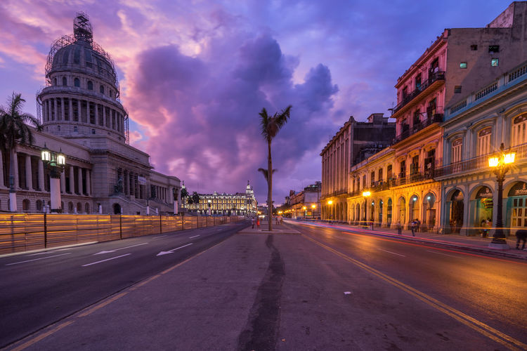 Illuminated street by el capitolio against sky