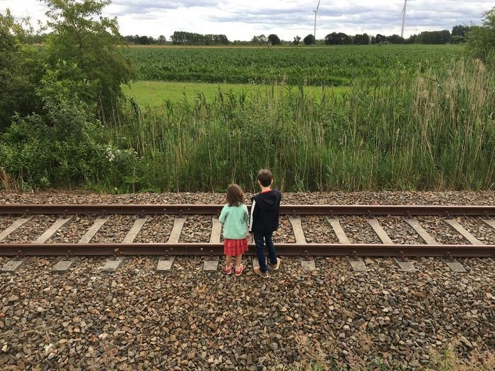 Rear view of friends on railroad track