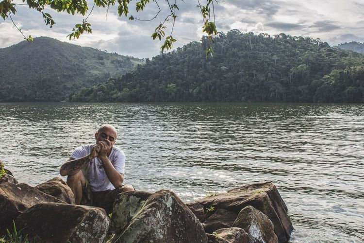 Mid Adult Man Smoking While Sitting On Rock By Lake Against Sky