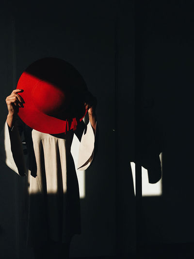 Midsection of woman holding hat while standing in darkroom