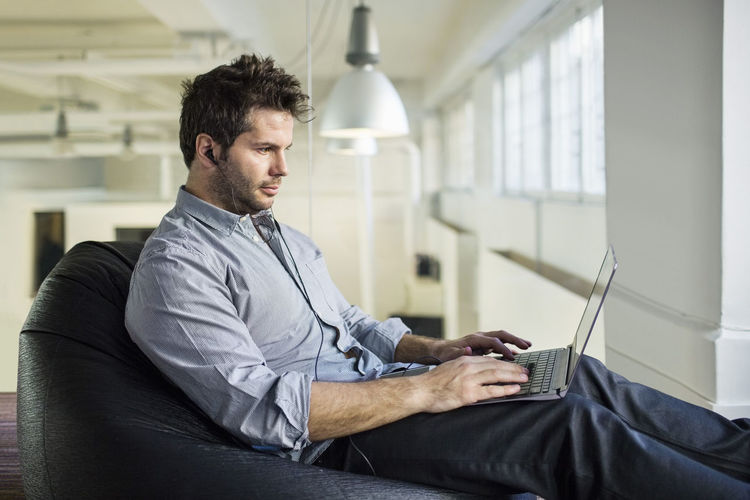 Side view of young man using mobile phone while sitting on sofa