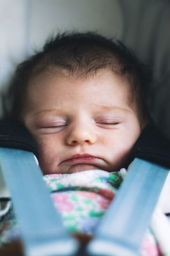 Close-up of cute baby girl sleeping on baby stroller