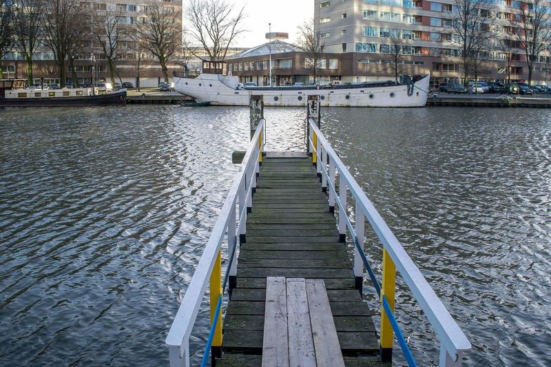 Jetty at river with buildings in distance