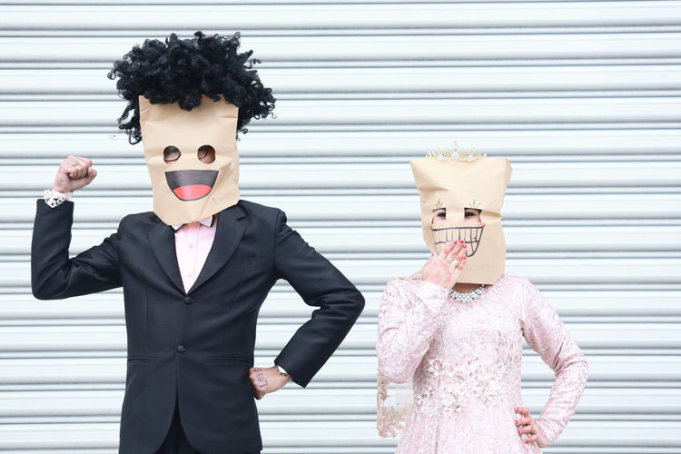 Young couple wearing paper bags while standing against wall