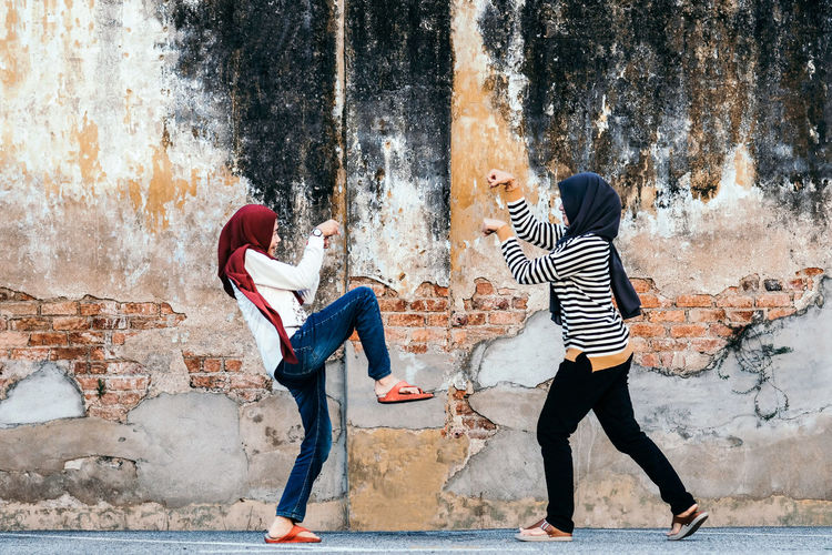 Full Length Casual Clothing Togetherness Young Adult Women People Architecture Lifestyles Leisure Activity Day Young Women Built Structure Positive Emotion Outdoors Woman In Hijab Martial Arts Self Defence Action Energetic Protection Abandoned Places Aggression  International Women's Day 2019