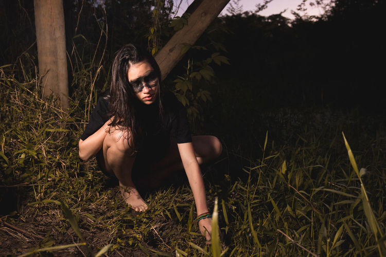 Young woman crouching by plant