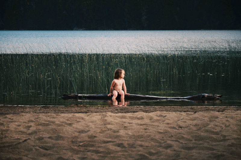 The boy in the trunk Alone Isolated Lakeview Nature_collection Boys Child Childhood Day Full Length Lake Land Leisure Activity Males  Men One Person Outdoors Patagonia Argentina Plant Real People Sandy Beach Shirtless Tranquility Scene Trunk Tree Water Be Brave A New Beginning