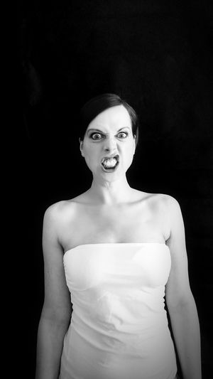 Portrait Of Angry Woman Standing Against Black Background