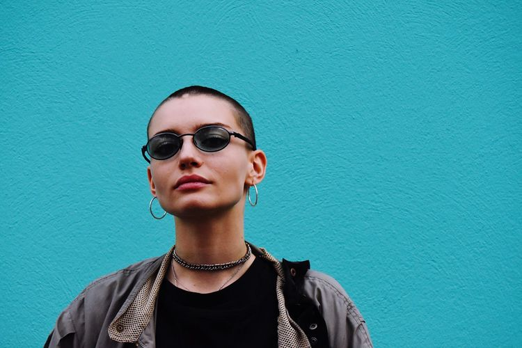 Portrait Of Woman Wearing Sunglasses Against Blue Wall