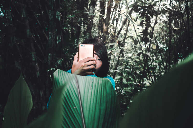 People Lifestyles Tree Technology Communication Wireless Technology Photography Themes One Person Smart Phone Photographing Forest Real People Connection Activity Using Phone Leisure Activity Outdoors WoodLand Selfie Portrait Surrealism Woman Mobile Phone Plant Posing My Best Photo