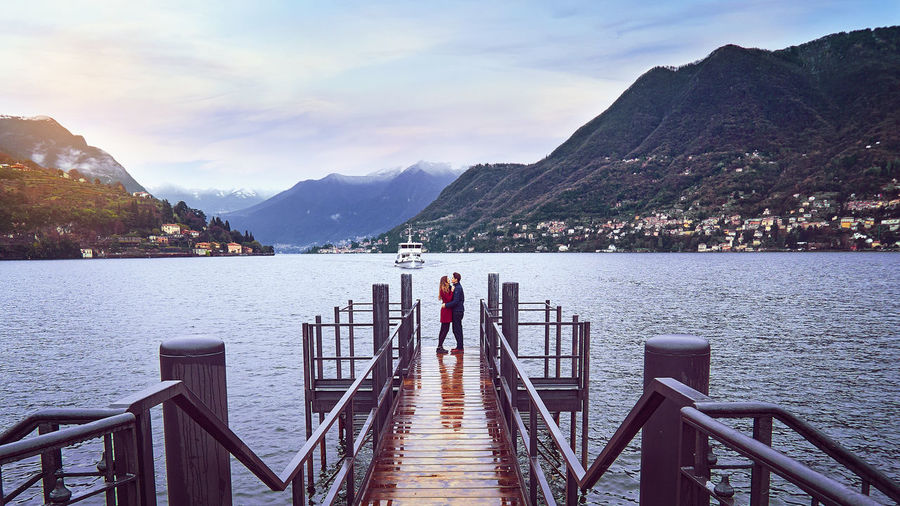Side view of couple embracing pier on lake against sky