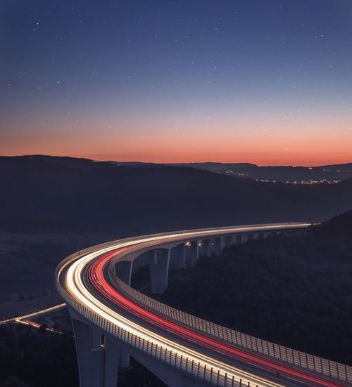 High angle view of light trails on bridge against sky at night