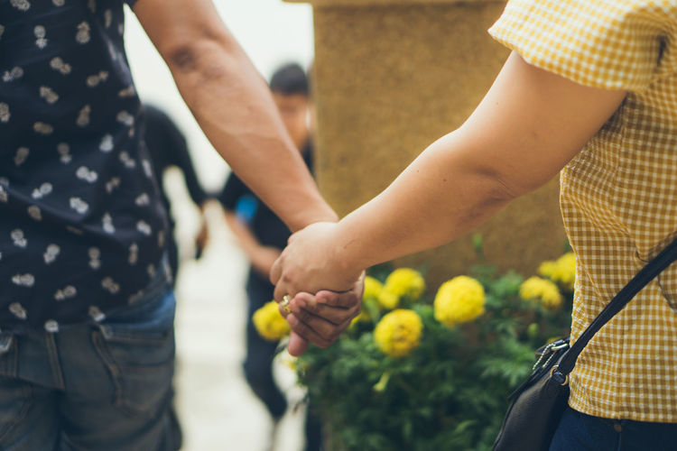 Midsection of couple holding hands standing outdoors