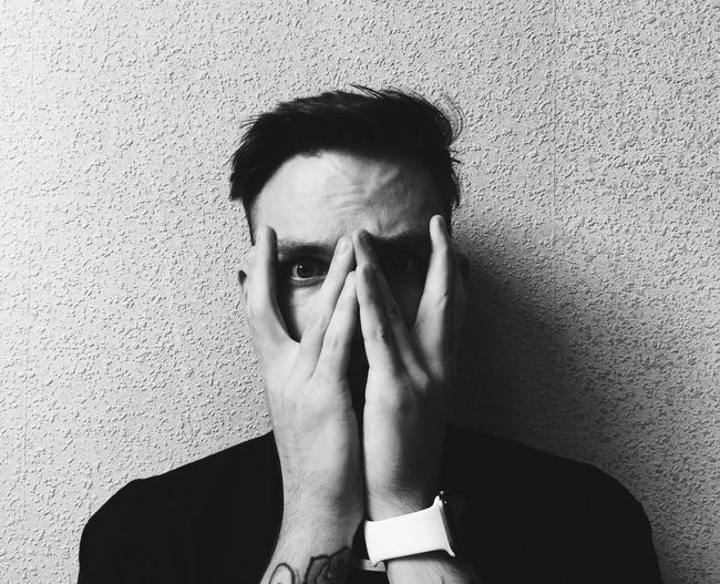 Portrait Of Young Man Covering Face With Hands While Standing Against Wall
