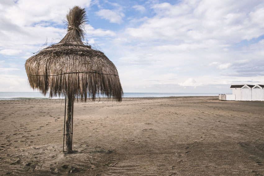 Holidays are over.... Desolate Wood Beach Beauty In Nature Brown Cloud - Sky Day Horizon Over Water Land Nature No People Only One Outdoors Sand Scenics - Nature Sea Sky Thatched Roof Thatched Umbrella Tranquil Scene Tranquility Umbrella Water Wet