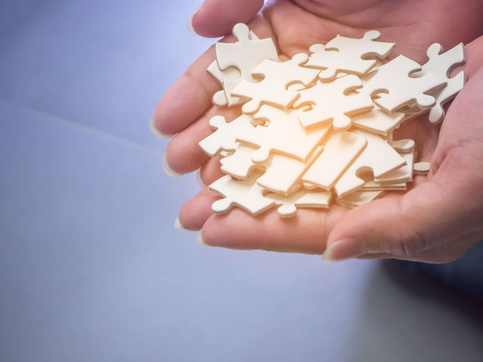 Jigsaw puzzle pieces on palm with sunlight effect. Blue Background Body Part Close-up Finger Food Food And Drink Hand Holding Human Body Part Human Hand Indoors  Indulgence Jigsaw  Jigsaw Piece Jigsaw Puzzle Leisure Activity Lifestyles One Person Real People Shape Sunlight Effect Sweet Sweet Food Temptation Unrecognizable Person