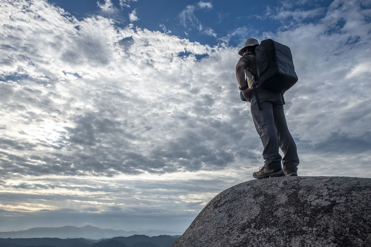 Rear view of backpack man standing on cliff against cloudy sky