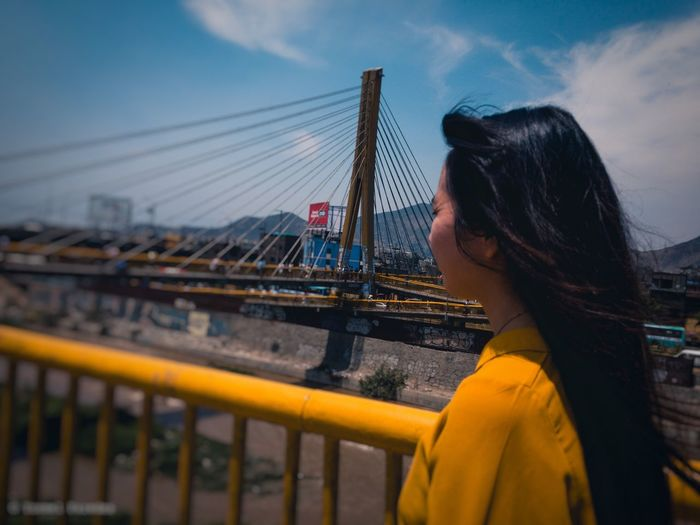 Side view of woman standing on bridge against sky