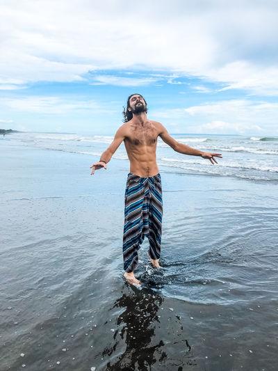 Full length of shirtless man standing at beach