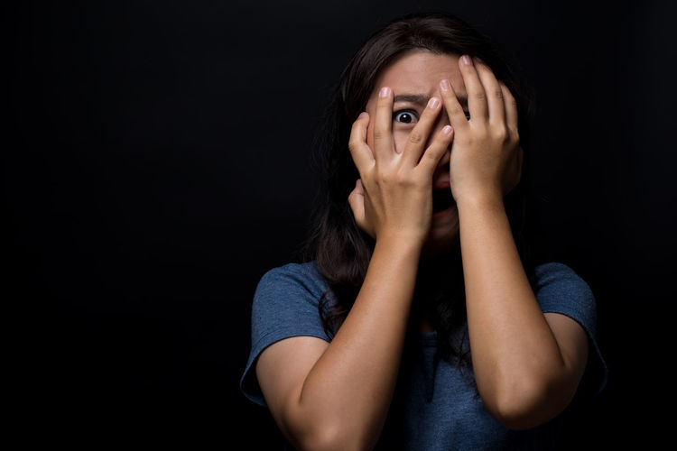 Portrait Of Scared Young Woman Hiding Face Standing Against Black Background