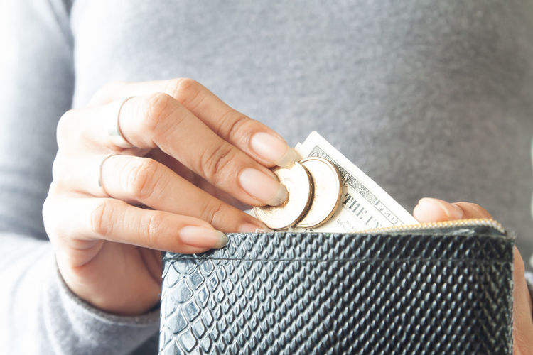 Close-up of woman hand inserting money in wallet