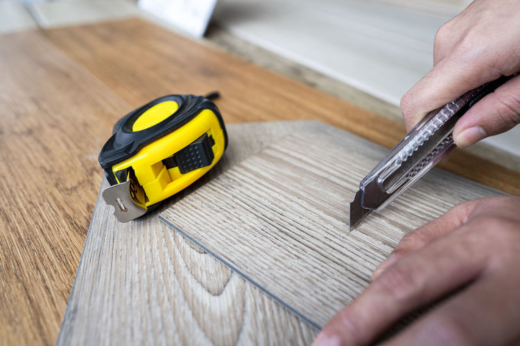 Vinyl floor tiles sheet use as home floor DIY easy to install for renovate item Unrecognizable Person Lifestyles Selective Focus Leisure Activity Tool Focus On Foreground Finger Table Close-up Work Tool Wood - Material Yellow One Person Indoors  Holding Construction DIY Vinyl Flooring Vinyl Floor Tiles Vinyl Floor Sheet Home Decoration  Renovation